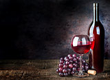 Glass of red wine with grapes and bottle