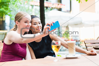 Young fashionable woman taking selfie with phone in cafe