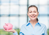 horizontal portrait of a successful woman with a pink piggy bank