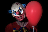 scary evil clown with a red balloon