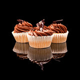 Three muffin cupcake with brown cream and pieces of chocolate