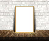 3D blank picture frame on a wooden table leaning against a brick
