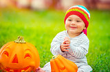 Cute baby playing with pumpkins