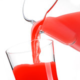 Pouring delicious red juice in glass