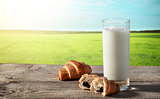 Glass of milk on rustic table with croissants
