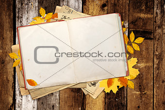 Old book and autumn leaves on wooden boards