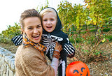 smiling modern mother and daughter on Halloween outdoors