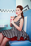 Retro (vintage) portrait of cheerful beautiful young girl sitting in cafe and drinking beverage. Pin up style portrait of young girl in dress