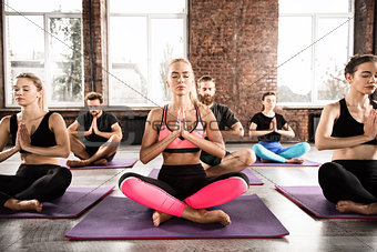 Yoga meditation of young people in lotus pose in fitness center