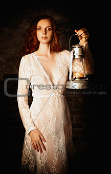 Portrait of sexy redhead woman with kerosene lamp