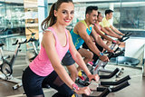 Beautiful fit woman smiling during cardio workout at indoor cycl