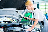 Female mechanic working in car workshop