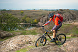 Cyclist in Red Riding the Bike on Autumn Rocky Trail. Extreme Sport and Enduro Biking Concept.