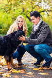 Couple with dog enjoying autumn in nature