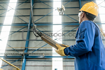 Skilled Asian worker controlling industrial hook