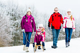 Family with kids having winter walk in snow