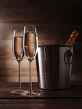 Image of two wine glasses with champagne, steel bucket and bottle