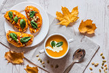Pumpkin cream soup. Vegan healthy food. Breakfast or brunch on white wooden background