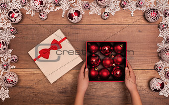 Child opening christmas present with red baubles