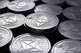 Ethereum coins (ETH) in blurry closeup.