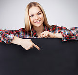 Young Smiling teenager blond girl hold black blank paper and shows on it.