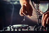 DJ playing music at mixer, hands closeup