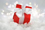 Christmas gift nestled in snow against a bokeh lights background