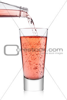 Pouring pink soda lemonade from bottle to glass