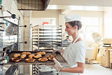 Baker woman getting bakery products out of oven