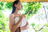 Woman draped in bath towel waiting for tropical sun