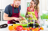 Man and woman cooking vegetarian dish together