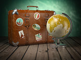 Old suitcase with globe on wood  background. Travel or tourism c