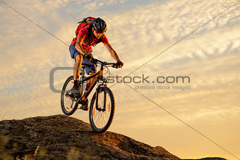 Cyclist in Red Riding the Bike Down the Rock at Sunset. Extreme Sport and Enduro Biking Concept.