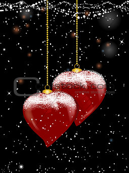 Christmas baubles heart shaped and snow on festive background