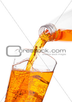 Pouring orange energy drink from bottle to glass