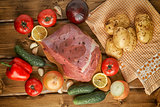 Raw beef with potatoes and vegetables on wooden boards