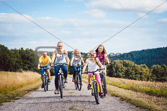 Family riding their bicycles on afternoon in the countryside
