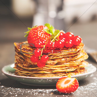 Homemade pancakes with fresh berries and honey