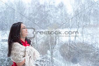 Brunette woman enjoying the snowfall