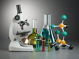Microscope with flasks, vials and model of molecule. Chemistry o