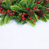 Christmas wreath with pine cones and berries nestled in snow
