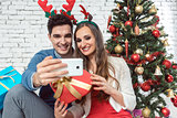 Couple making selfie photos with phone on Christmas