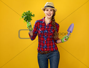 smiling woman grower with fresh parsley and gardening tool
