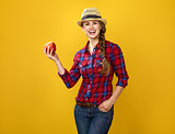 woman grower isolated on yellow background showing an apple