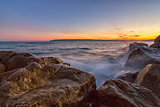 Sunset over the sea with splash waves on the rocks