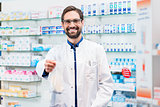 Pharmacist in pharmacy selling pharmaceuticals in bag