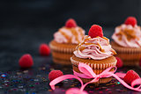 Raspberry and caramel cupcakes on dark background