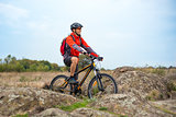 Happy Cyclist in Red Resting on the Bike on Rocky Trail. Adventure Sport and Travel Biking Concept.