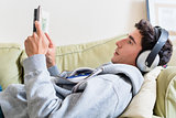 Relaxed young man lying down on the couch while reading a book a