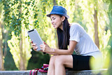 Asian woman using a tablet PC outdoors